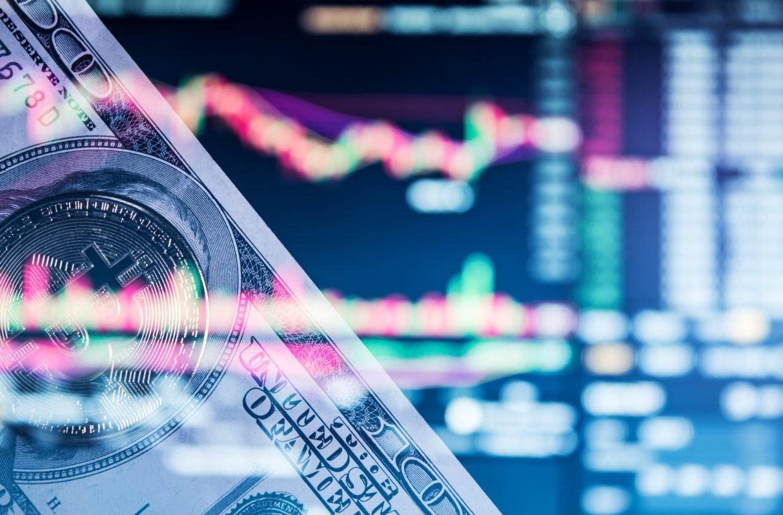 Abbildung eines Bitcoin, einer Dollarnote vor einem Kursdiagramm