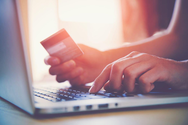 Person zahlt mit Krypto-Karte vor einem Computer